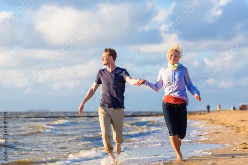 canvas print picture Paar rennt durch Wellen und Sand am Strand