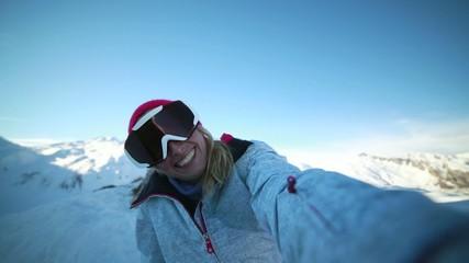 Woman on ski slopes taking selfie