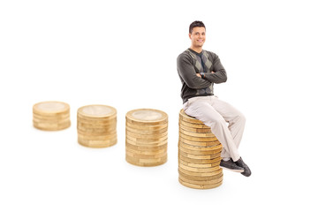 Casual man sitting on a pile of coins