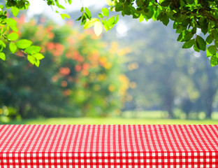 Table with red tablecloth and blur trees with bokeh background
