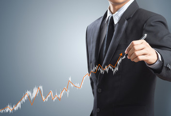 Business man drawing a growing graph concept