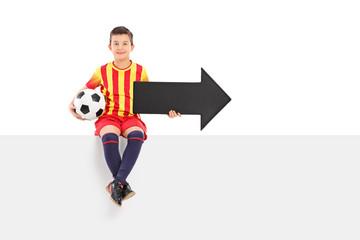 Junior athlete holding an arrow and a football