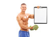 Man holding a broccoli dumbbell and a clipboard