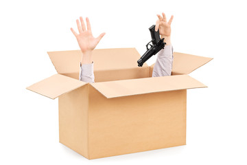 Hands surrendering gun and peeking from a box