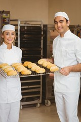 Team of bakers holding rack of rolls