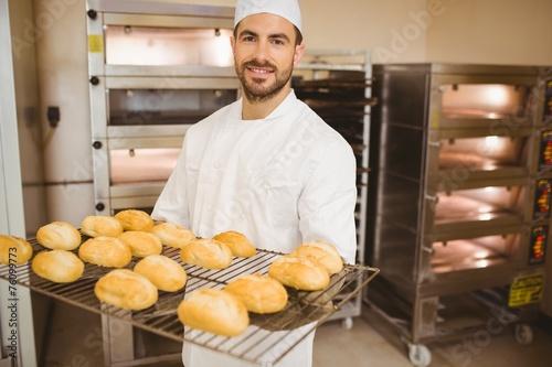 Papiers peints Table preparee Baker smiling at camera holding rack of rolls