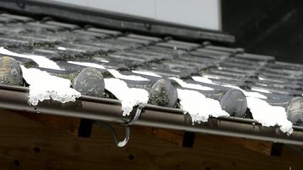 積もった雪の融けている瓦屋根
