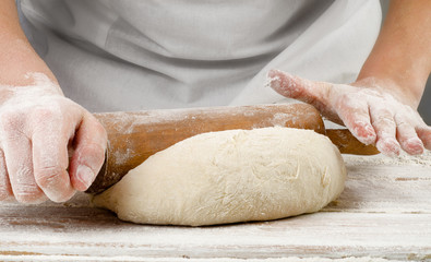 Hands preparing dough with rolling pin on wooden table