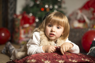 little girl leaned on a pillow holding a Christmas star