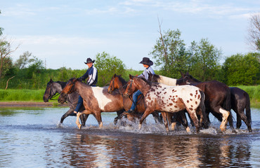 Two cowboys on horses ford the river
