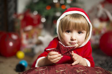 little girl in a Santa outfit leaned on a pillow holding a star
