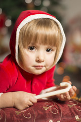 close up of a little girl in Santa outfit holding a lollipop
