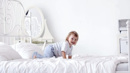 cheerful toddler somersault on the bed