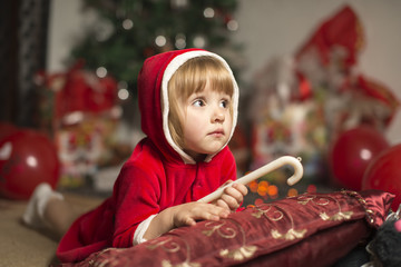 girl in a Santa costume laying on a pillow holding a lollipop