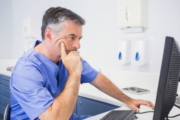 Serious dentist sitting and using computer