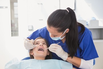Pediatric dentist using dental explorer and angled mirror