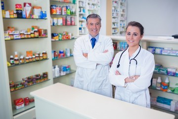 Smiling pharmacist and his trainee with arms crossed