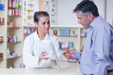 Trainee giving a bag of pills to a customer