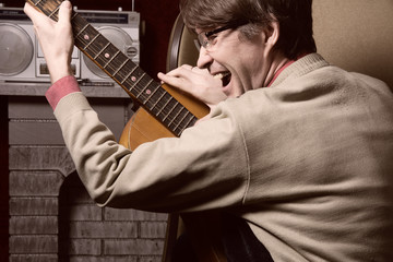 Adult cheerful man with acoustic guitar.