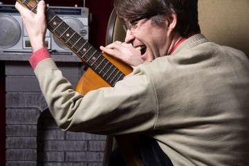 Adult cheerful man with acoustic guitar