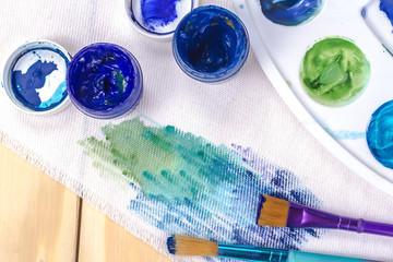 голубые краски, кисть и холст художника