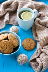 A cup of tea with lemon, biscuits, beige knitted blanket