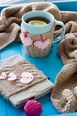 A cup of tea in sweater, old notebook with hearts of felt