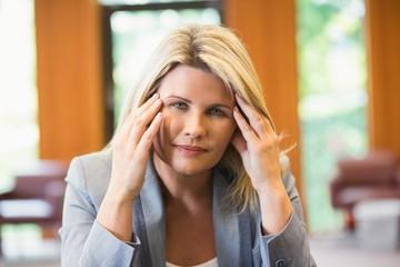 Blonde businesswoman getting a headache
