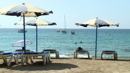 Parasols and sun loungers in a beach of the Mediterranean sea