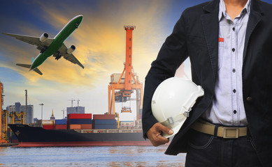manager man holding safety helmet standing against ship and cont