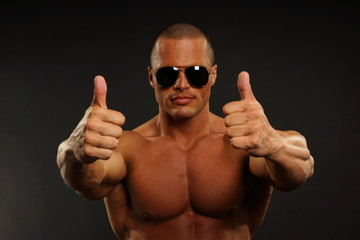 Handsome muscular man in sunglasses shows you thumbs up