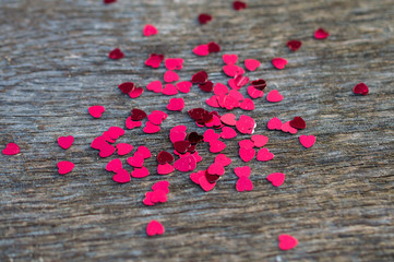 heart confetti on wood table /glitter background