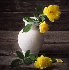 yellow roses on wooden background