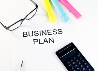 business plan words near highlighters, calculator and glasses