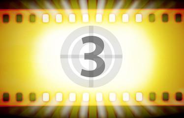 Cinema film strip with movie countdown and light rays.
