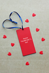 Red gift tag with typewriter HAPPY VALENTINES DAY and blue ribbo