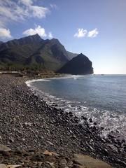 Playa de piedras con montañas al fondo