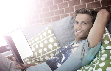 Young man in apartment reading book