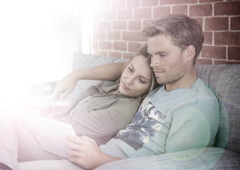 Young couple relaxing in sofa and using tablet