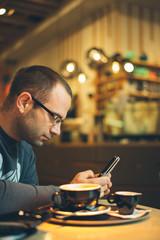 man in coffee shop using smart phone