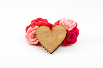 Wooden heart with pink and red wool flowers on white background