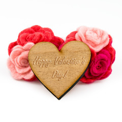 Wooden heart with carved words and red wool flowers on white