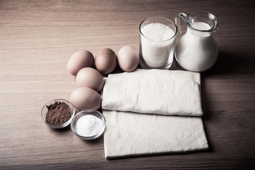 Milk, sugar, cocoa, puff dough, eggs and salt on a wooden board.
