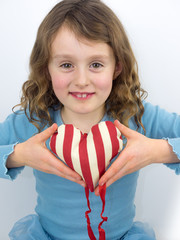 small girl smiling and holding a valentine heart