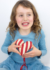 little girl laughing and holding a valentine heart