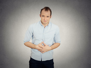 man, doubling over in acute body stomach pain grey background