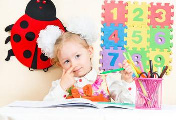 Cute child girl drawing in preschool