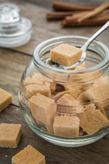 Brown sugar cubes in spoon on jar