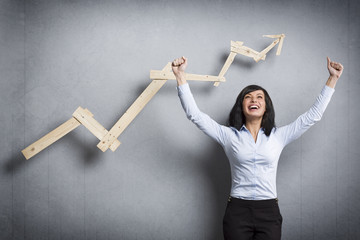 Overjoyed businesswoman in front of ascending business graph.