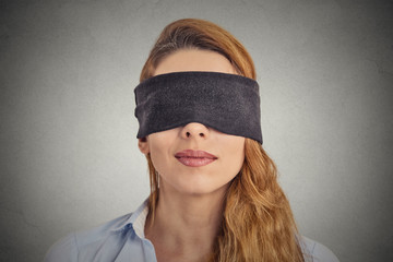 Headshot blindfolded red haired woman on grey background